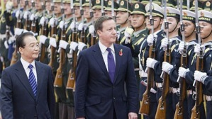 David Cameron - wearing the poppy - inspects Chinese troops in Beijing with China's Premier Wen Jiabao